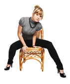 Young woman sitting on a chair — Stockfoto