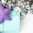 Purple star on top of a light blue gift - Stock Photo