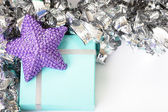 Purple star on top of a light blue gift — Stock Photo
