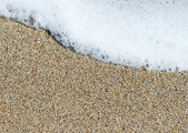 Sea foam wave on sand close up — Stock Photo