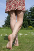 Woman legs relaxing on sunny garden — Stock Photo
