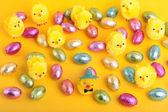 Pasen eieren en kuikens over geel — Stockfoto