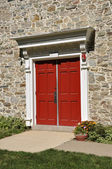 Stone church and red doors — Stock Photo