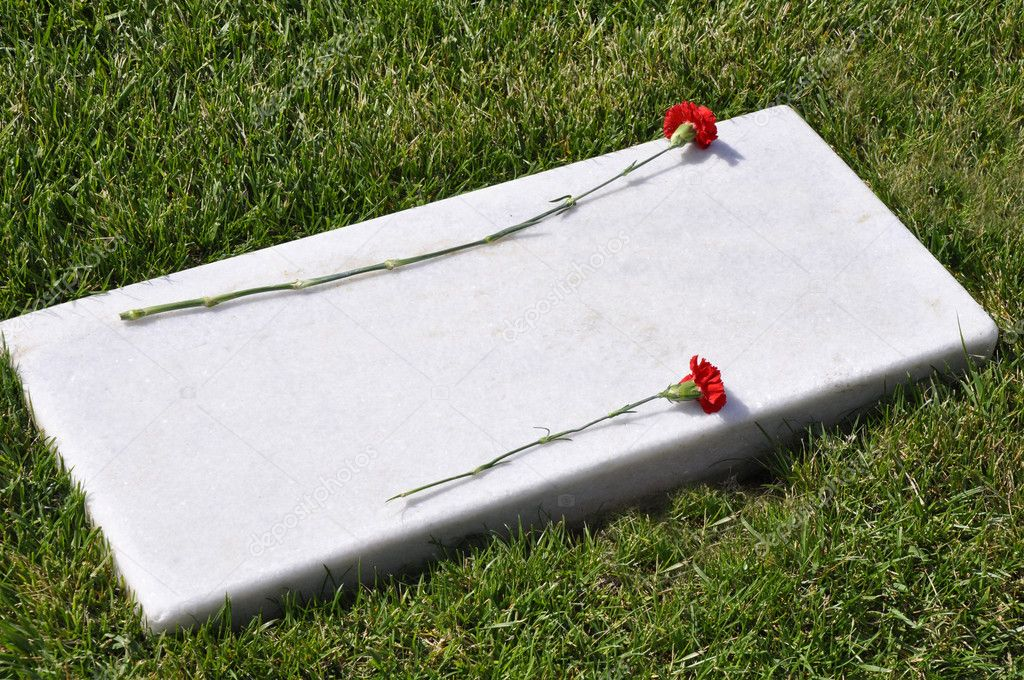 A flat marble tombstone with two red carnation flowers laying on it — Stock Photo #2348452