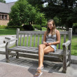 Teenage girl on outdoor bench — Stock Photo