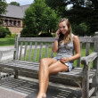 Teenage girl sitting on bench with phone — 图库照片