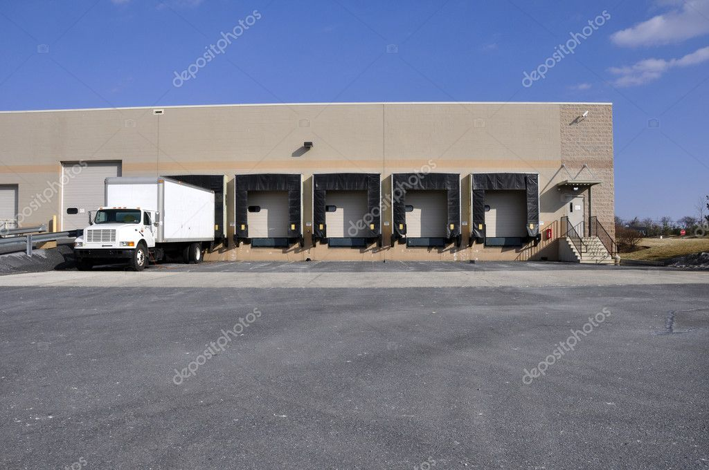Many empty bays and truck at a warehouse unloading dock — Stock Photo #2368428