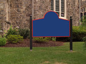 Blank sign by a stone building — Stock Photo
