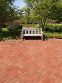 Empty wood bench by a brick patio — Stock Photo
