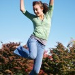 Teenage girl jumping in the air - Stock Photo