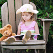 Child Reading to Teddy Bear - 图库照片