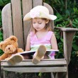 Child Reading to Teddy Bear - Stok fotoğraf