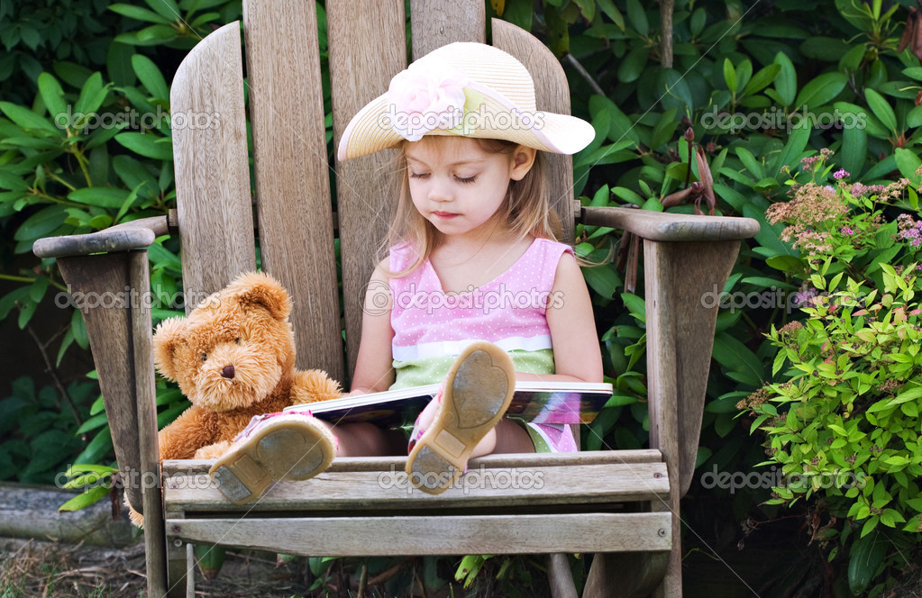 Little girl pretending to read to her teddy bear  — Stock Photo #2593330