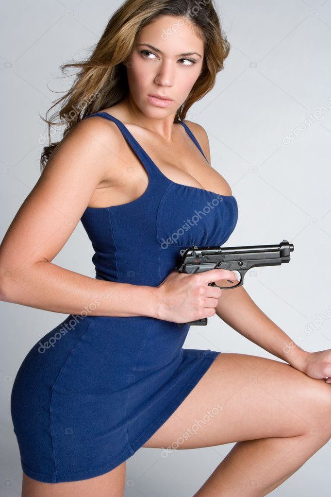 Beautiful young woman holding gun  Foto de Stock   #2401157
