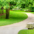 Stone bench on a gravel path - Stock Photo
