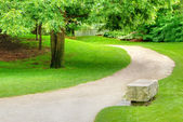 Stone bench on a gravel path — Stock Photo