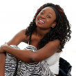 Black woman sitting on bed laughing — Stockfoto