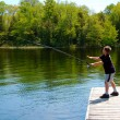 Boy fishing on a dock — Stock Photo