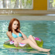 Young woman floating in swimming pool — Stock Photo