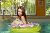Brunette woman in a water floating tube — Stock Photo