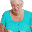 Senior woman confused with many remotes — Stock Photo
