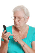 Senior woman dialing number cell phone — Stock Photo