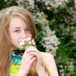 Young female teenager smelling flowers — Stock Photo #2438998