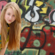 Young female teenager with graffiti back — Stock Photo