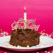 Chocolate birthday cake on pink — Stock Photo
