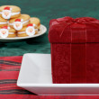 Christmas present on plate with cookies — Stock Photo