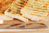 Closeup garlic bread with knife — Stock Photo