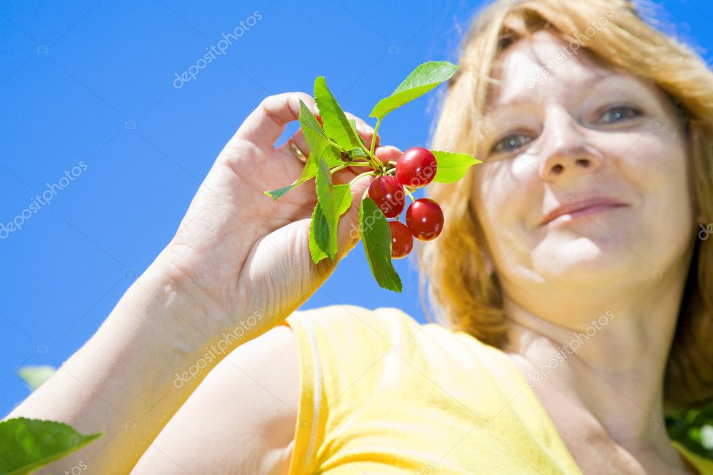 A beautiful woman shows off freshly picked bunch of tart cherries. — Stock Photo #2451510