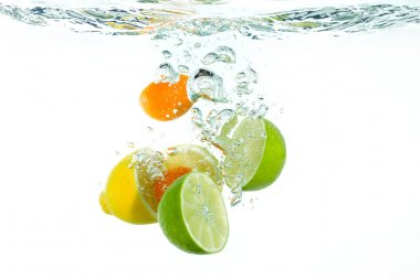 Citrus fruit falling into clear water