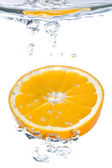 An orange slice falling into clear water — Stock Photo