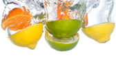 Citrus fruit falling into clear water — Stock Photo