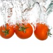 3 tomatoes falling into clear water — Stock Photo #2436019