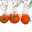 Foto Stock: 3 tomatoes falling into clear water