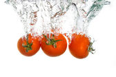 3 tomatoes falling into clear water — Stock Photo