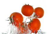 Tomatoes jumping out of the clear water — Stock Photo