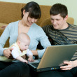 Happy family with laptop — Stock Photo