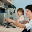 Mother with daughter working on computer - Stockfoto