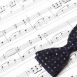 Bow tie on musical notes paper - Stock Photo