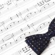 Stock Photo: Bow tie on musical notes paper