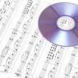 CD on sheet music. Digital music concept. - Stock Photo