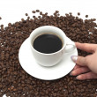 Cup with coffee and hand over coffee beans - Stock Photo