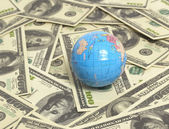 Globe on US hundred dollar bills — Stock Photo