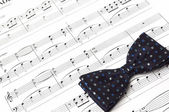 Bow tie on musical notes paper — Stock Photo
