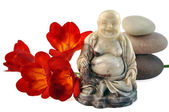 Laughing Buddha, freesia and stones. — Stock Photo