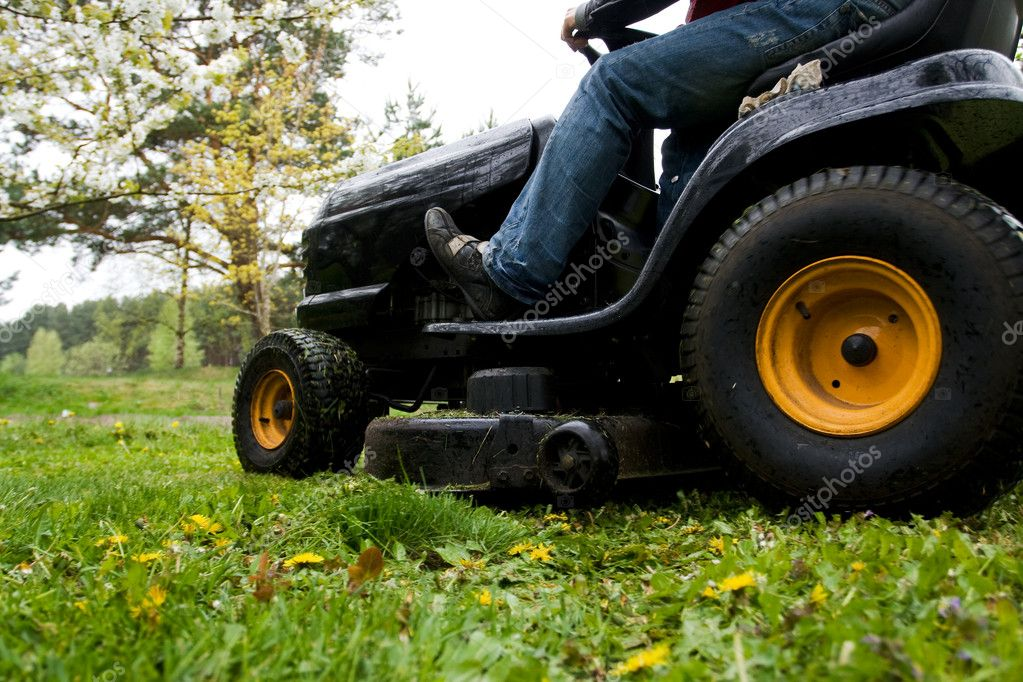 Worker mowing with black riding lawn mower — Stock Photo #2386230