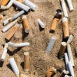 Stock Photo: Cigarette butt in sand
